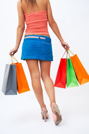 woman with beautiful legs holding shopping bags in hands photo