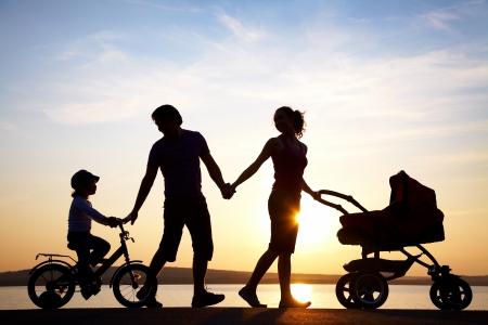 recien nacidos: Siluetas de padres felices tener buen tiempo con sus hijos peque?os en la costa