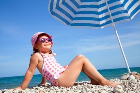happy little girl at the seaside under an umbrella in the summer photo