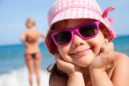 gafas de sol: ni�a feliz en la playa bajo una sombrilla en el verano