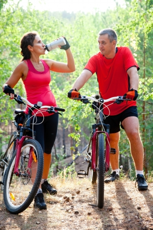 outdoor pursuit: Mature Couple Biking Together in the Park