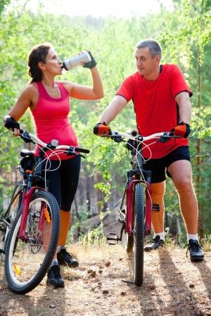 hombres haciendo ejercicio: Pareja madura juntos en bicicleta en el parque
