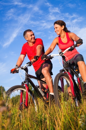 healthy couple: Couple of cyclists riding bicycles in meadow Stock Photo