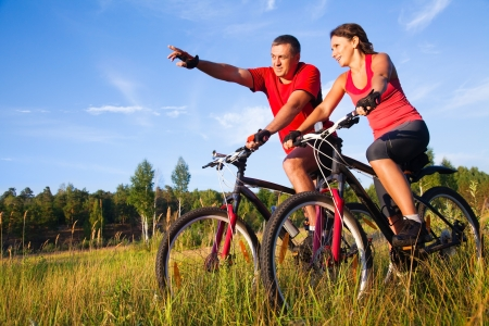pareja saludable: Pareja de ciclistas que pedalean bicicletas en el prado Foto de archivo