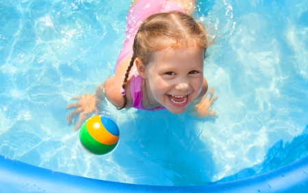 Portrait of cute little girl in swimming pool outdoors photo