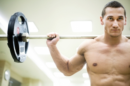 strong man holding barbell on your shoulders in gym Stock Photo - 19774149