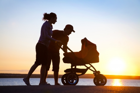 baby stroller: Silhouettes of parents loving  their child in a stroller Stock Photo