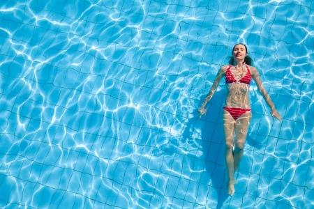 Young woman relaxing in the swimming pool photo