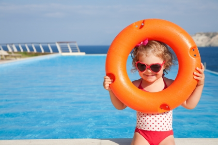swimming at the beach: little girl in swimsuit takes lifebuoys backgraund swimming pool