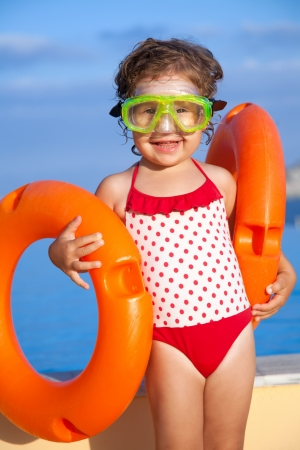 little girl in a mask for  diving takes lifebuoys in pool photo
