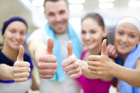 the wellbeing:  young sporty people show  OK   in gym  Stock Photo