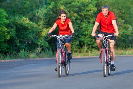 happy mature couple riding a bicycle in park photo