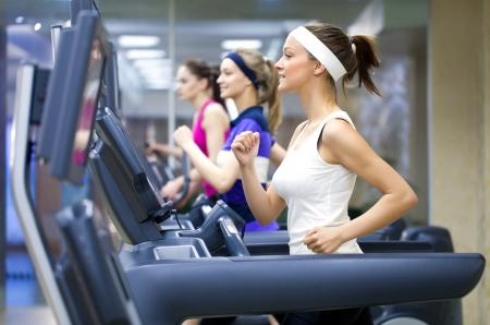 Grupa młodych ludzi działa na bieżni w siłowni