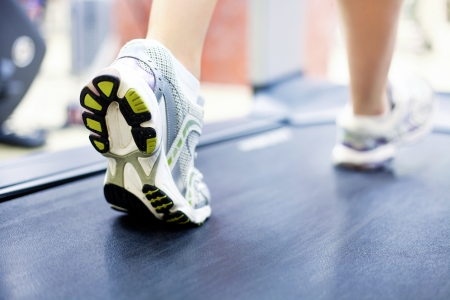 moving activity: womans muscular legs on treadmill, closeup