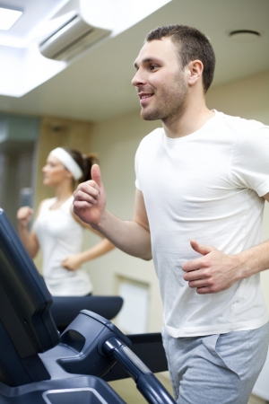 Healthy couple running on a treadmill in a sport centre  Stock Photo - 19774037