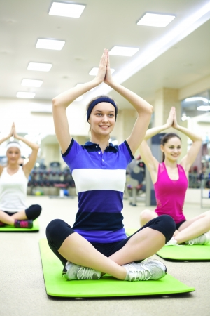 group of young women doing yoga in  gym photo