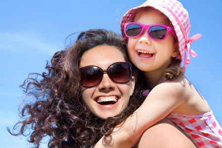 sunglasses beach: little girl and her mother have  a good time at the seaside resort