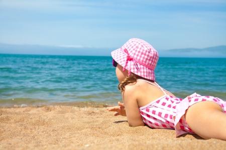 little girl lying on the beach and sunbathe in the sun photo