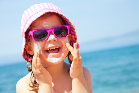 child swimsuit: Girl anoints her face protective cream on the beach