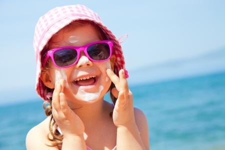 Mädchen salbt ihr Gesicht schützende Creme am Strand