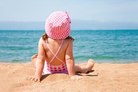 little girl lying on the beach and sunbathe in the sun