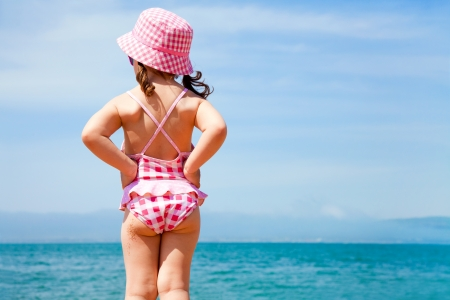 child on the beach:  little girl in a swimming suit looks at the sea