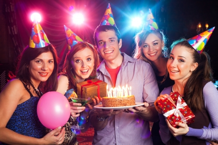 dance bar: young company holds a cake with candles on birthday