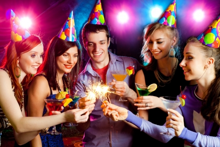 birthday adult: young company celebrates the holiday with fireworks in the hands
