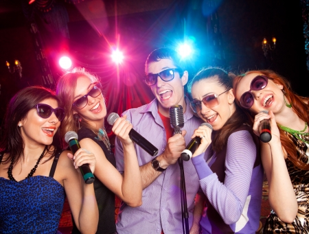 singer:  group of young people singing into  microphone at  party. karaoke