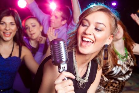 zábava: Mladá dívka zpívá do mikrofonu na party Reklamní fotografie