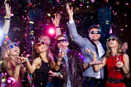 축하: 쾌활한 젊은 사람들이 클럽 파티에 색종이 샤워.