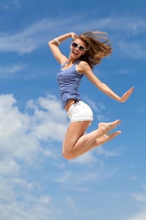 junge Glück Frau gegen blauen Himmel springen