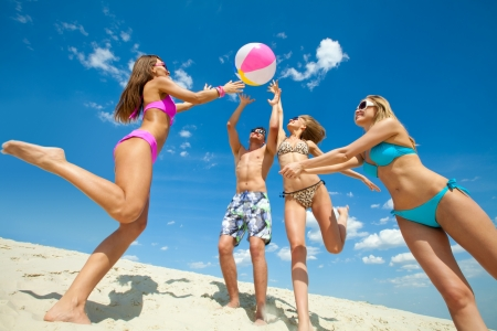 teens playing: Young fun people are playing ball on the beach Stock Photo
