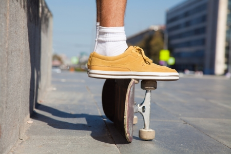 Close up of a skateboarders feet while skating on concrete at the skate park  photo