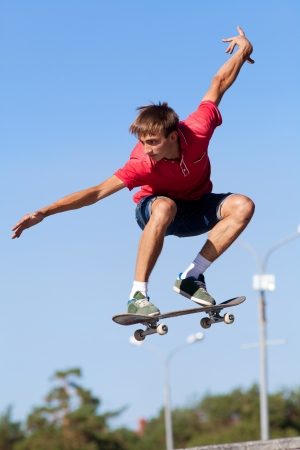 skateboarder: cool skateboard is jumping high in air  Stock Photo