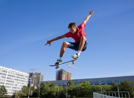 skateboarding: cool skateboard is jumping high in air  Stock Photo