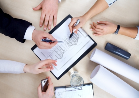 architect plans: Hands of business people at the table at the meeting in the office. top view