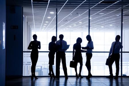 silhouettes de gens d'affaires se pr?cipiter pour les grandes fen?tres en arri?re-plan