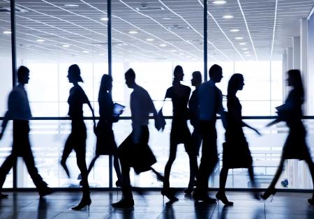 conferentie: silhouetten van mensen uit het bedrijfsleven haasten voor de grote ramen in de achtergrond Stockfoto