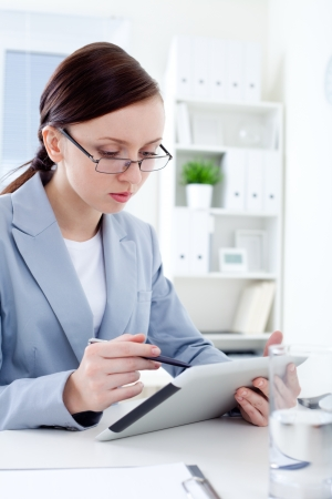 Young businesswoman reading  a digital tablet photo