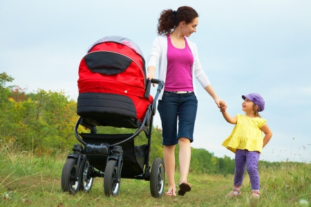 upbringing: happy mother with little daughter and pram are walking in park
