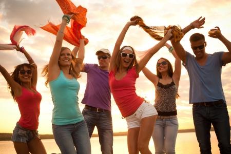 juventud: Gran grupo de jóvenes disfrutando de una fiesta en la playa Foto de archivo