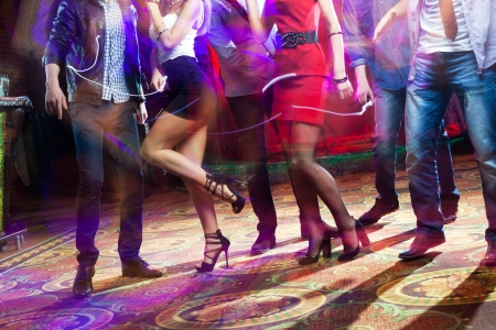 feet of people dancing on a club party  unrecognizable