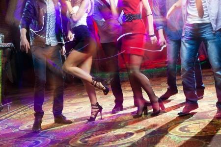 danza moderna: pies de personas bailando en una fiesta del club irreconocible