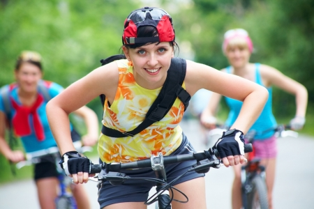 road cycling: Young pretty women  race on bicycle in green park