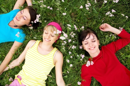 Young pretty women resting on the green grass in summer Stock Photo - 21462466