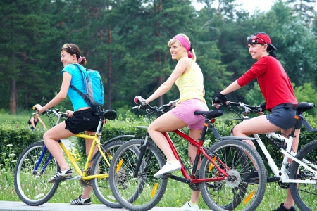 Young pretty women  race on bicycle in green park photo