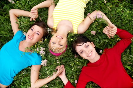 Young pretty women resting on the green grass in summer photo