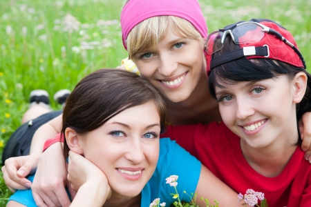 Portrait of three young  beautiful girl in sports clothes outdoor photo