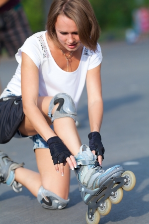 blading: Young woman putting on skates going rollerblading in urban city park  Stock Photo
